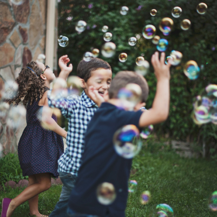 Play therapy represented by a picture of children playing amongst bubbles